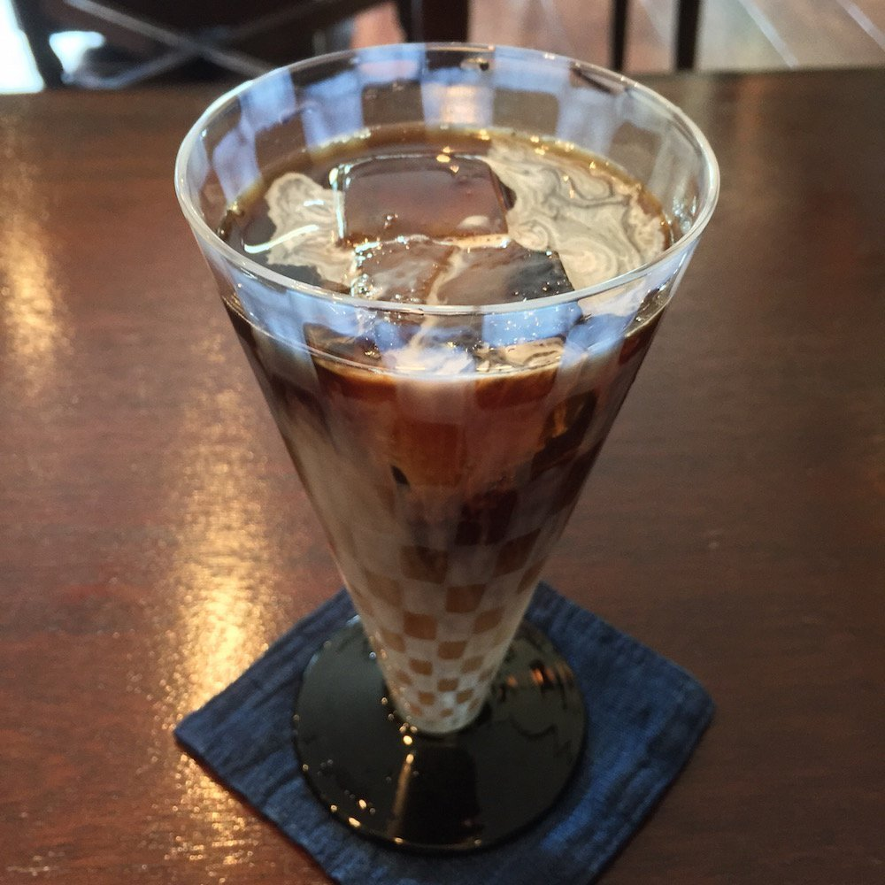 Iced coffee in a stylish glass and a wa-looking coaster