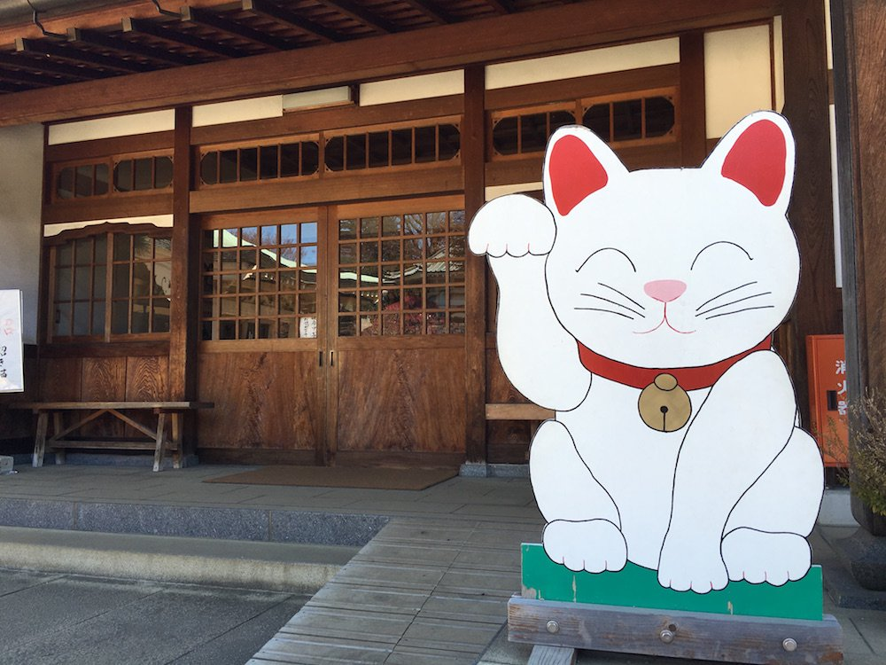 Maneki Neko welcomes you to the shop at the temple